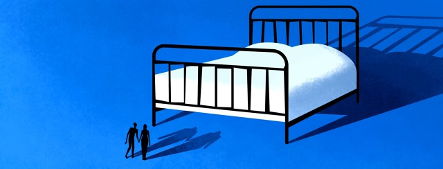 A man and woman holding hands look up at large bed