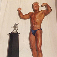 Advocate, Greg, posing with bodybuilding trophy after winning contest