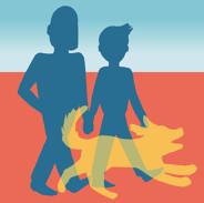 a couple walks with their dog