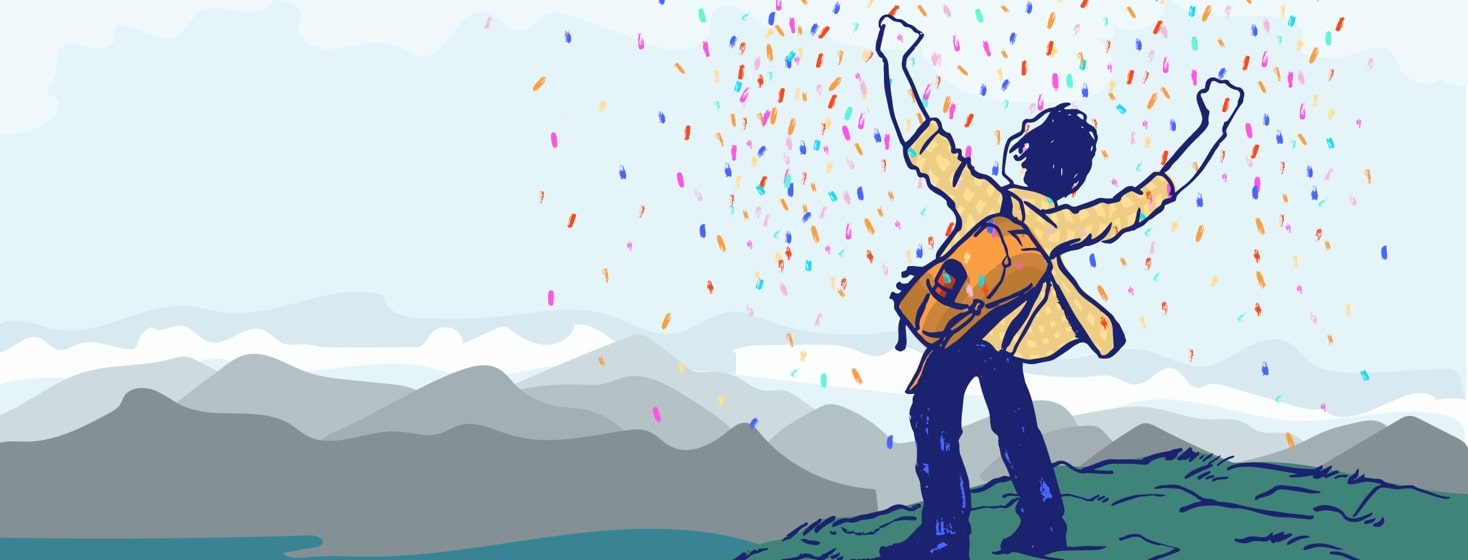 a man stands at the top of a mountain and is showered with confetti