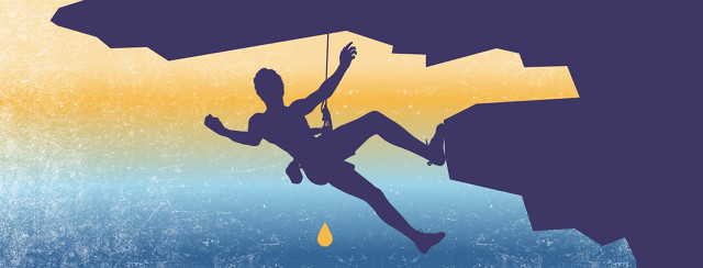 A man climbing with a yellow drop of liquid falling below him