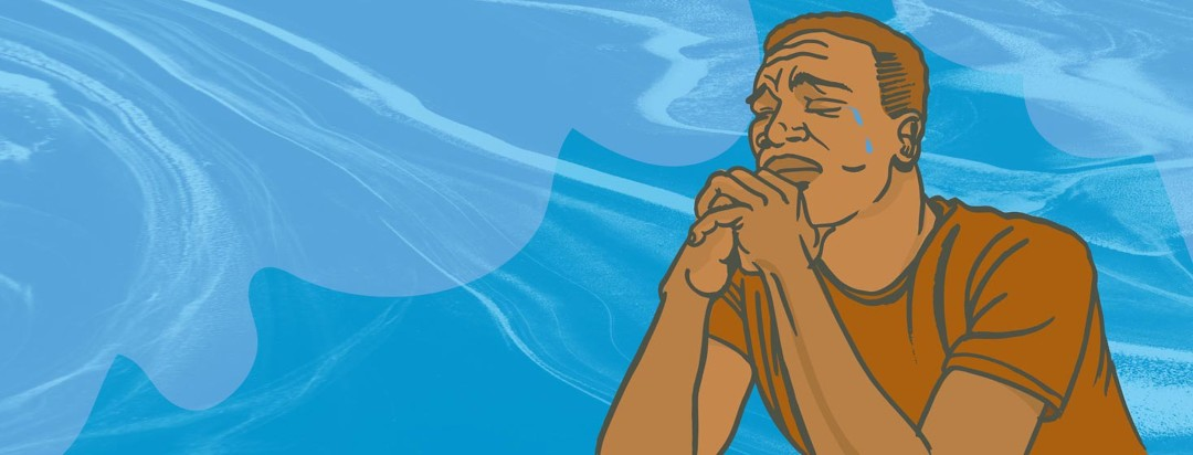 a man sits with his hands folded in front of him and cries