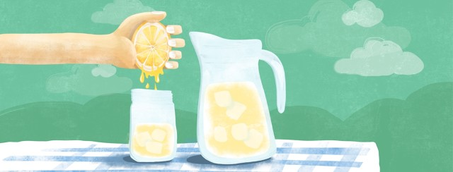 A hand squeezing a lemon into a glass next to a pitcher of lemonade.
