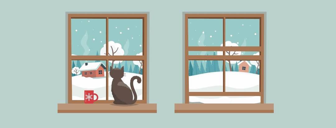 Two windows look out on a snowy winter scene.