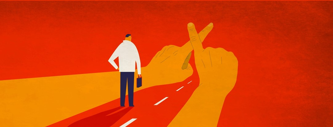 A man with a briefcase walks down a road that is blocked by two hands making an X sign with their fingers.
