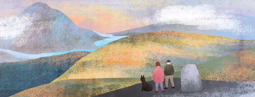 A man, woman and dog on a hike look out over a hill towards a vast green landscape with mountains and rivers.